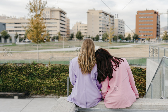 Woman leaning on sister's shoulder while sitting on rooftop against sky in city
