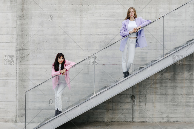 Sisters leaning on railing while standing over steps against wall