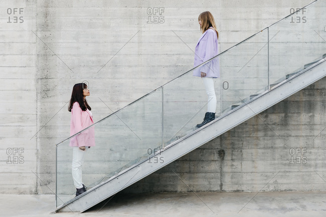 Young siblings looking at each other while standing on steps by wall
