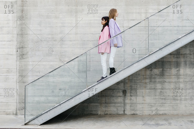 Young siblings back to back standing on steps by wall