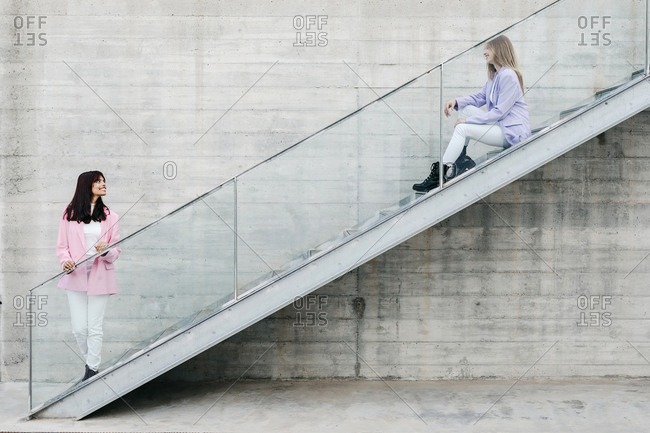Smiling woman looking at sister sitting on staircase