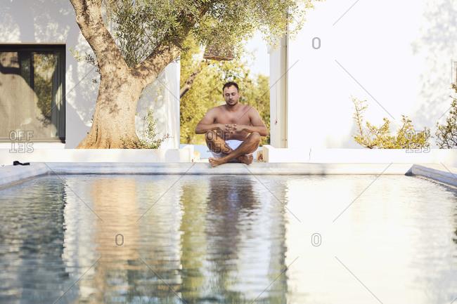 Shirtless young man meditating at poolside in backyard