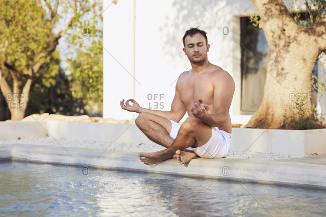 Young shirtless man in lotus position at poolside