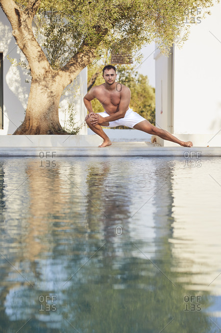 Shirtless young man stretching at poolside