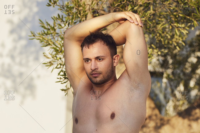 Shirtless man doing warm up exercise in backyard on sunny day