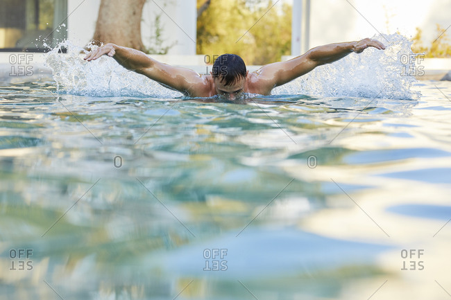 Young man doing butterfly stroke in swimming pool