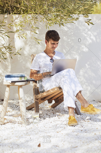 Young man working on laptop in backyard against wall