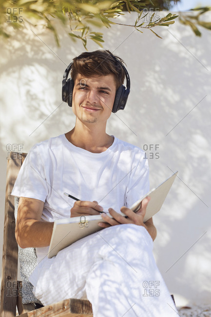 Smiling man thinking while listening to music against white wall in back yard
