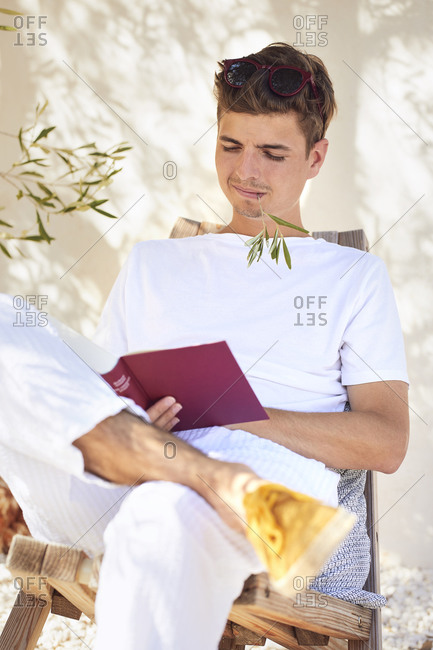 Young man with stem in mouth reading book against wall