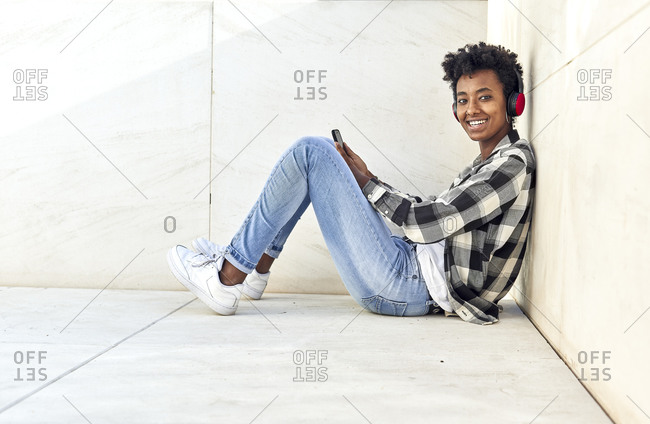 Smiling beautiful Afro woman sitting with smart phone against retaining wall