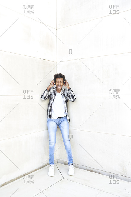 Cheerful young female hipster listening music through headphones while leaning against white wall