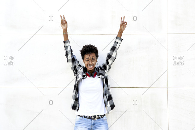 Cheerful female Afro hipster showing peace sign with arms raised against white wall
