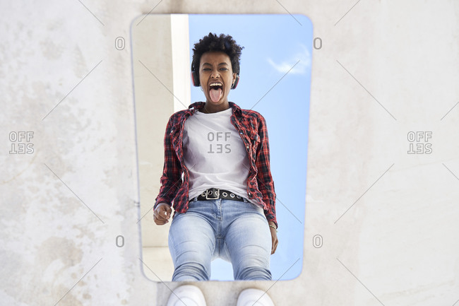 Cheerful young Afro woman sticking out tongue while reflecting on mirror