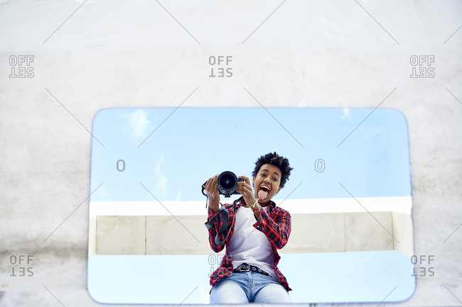 Playful young woman taking selfie from camera on mirror reflection