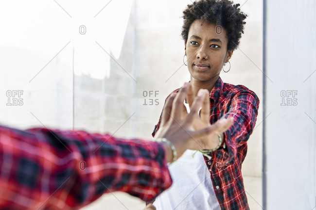 Young Afro woman with serious expression touching her mirror reflection