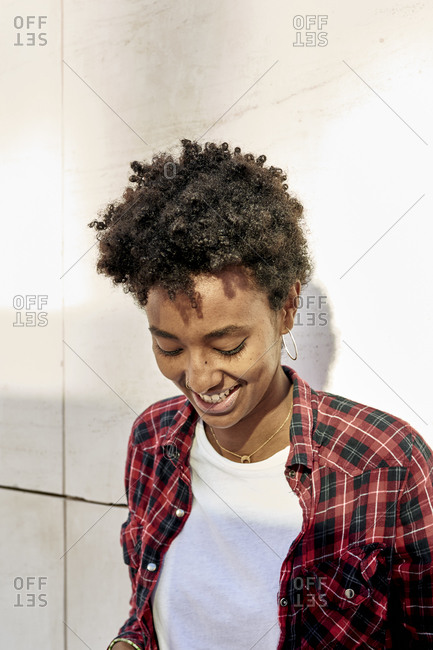 Smiling young Afro female hipster looking down against white wall