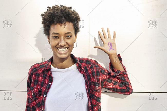 Cheerful young woman with purple awareness symbol on palm against white wall during Women's Day