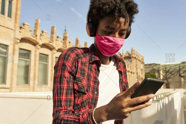 Afro young woman wearing pink sanitary mask while using smart phone during COVID-19
