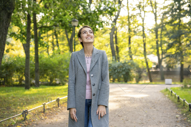 Smiling businesswoman looking up while walking in park