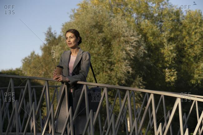 Female entrepreneur leaning on railing while standing over footbridge during autumn