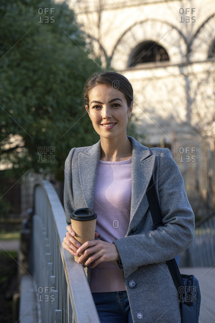 Smiling businesswoman holding coffee cup while standing on footbridge during autumn