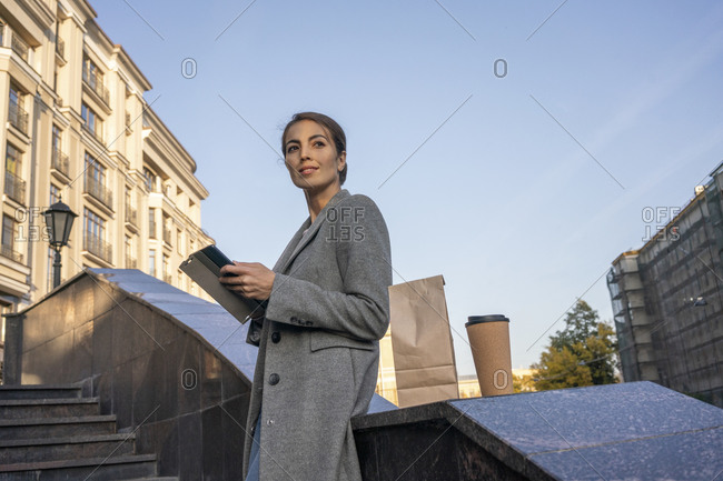 Businesswoman holding digital tablet standing on steps in city during autumn
