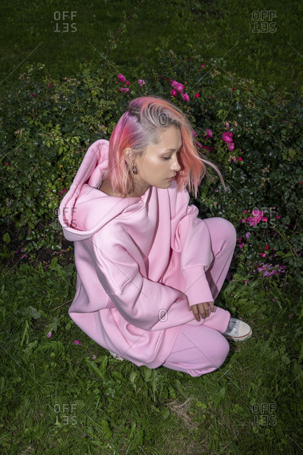 Youngwoman with pink hair wearing pink hooded shirt sitting on grass near rose bush