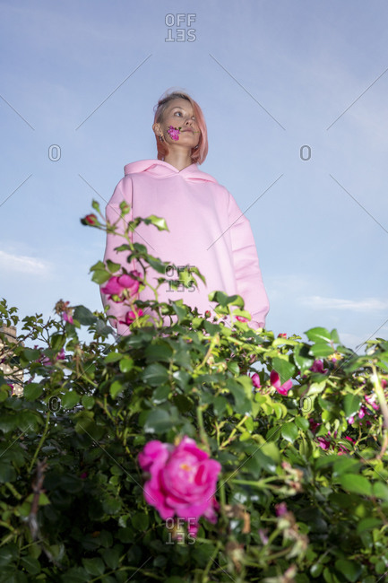 Young woman with pink hair wearing pink hooded shirt near rose bush