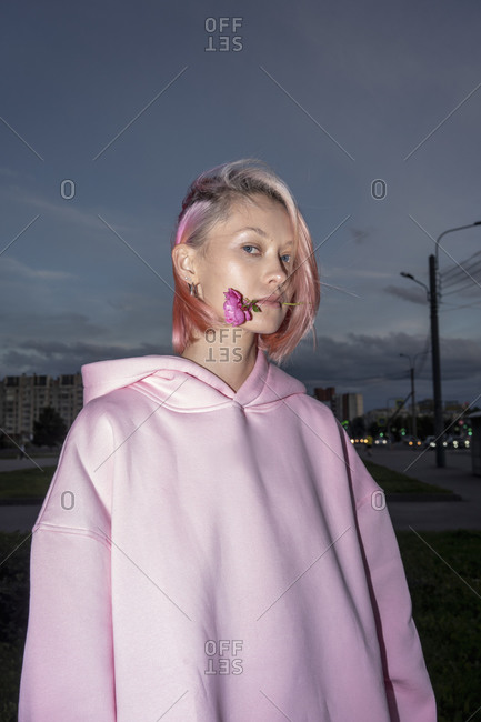 Portrait of youngwoman with pink hair wearing pink hooded shirt holding rose in mouth