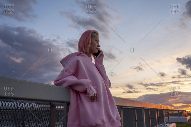 Young woman with pink hair wearing pink hooded shirt leaning against railing and talking on mobile phone