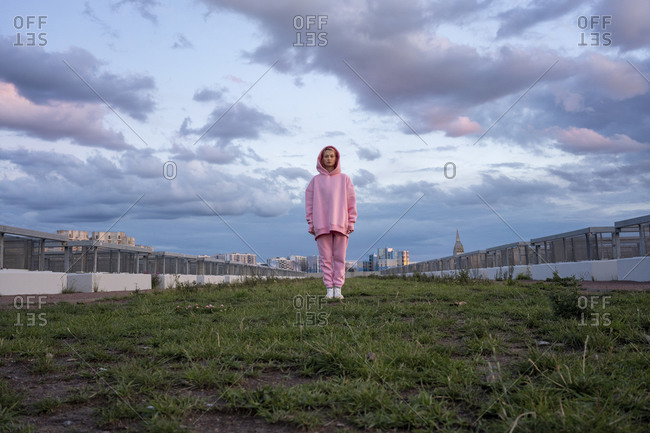 Portrait of young woman with pink hair wearing pink hooded shirt standing on grass