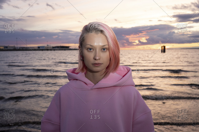 Portrait of young woman with pink hair wearing pink hooded shirt with sea at sunset in background