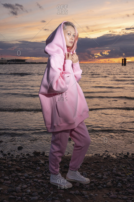 Portrait of young woman wearing pink hooded shirt standing on beach at sunset