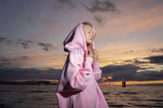 Young woman wearing pink hooded shirt standing on beach at sunset