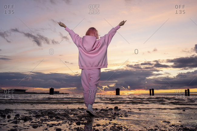 Rear view of young woman with pink hair wearing pink hooded shirt standing on beach at sunset