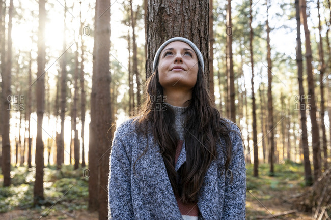 Thoughtful woman looking up while standing against tree trunk in Cannock Chase forest