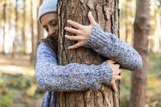 Female explorer embracing tree trunk while hiking in Cannock Chase woodland