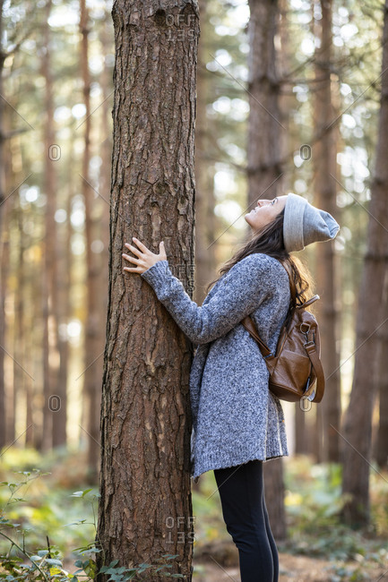 Woman looking at tree trunk while standing in Cannock Chase woodland during winter