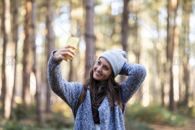 Smiling woman with hand behind head taking selfie while standing in Cannock Chase woodland