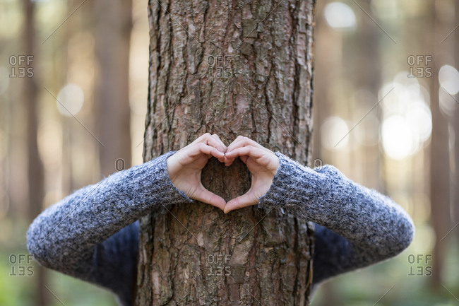 Woman embracing tree and making heart shape in Cannock Chase forest