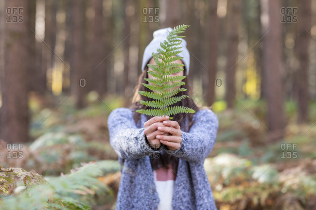 Woman covering face with fern leaf while standing in Cannock Chase forest