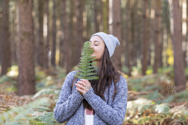 Female hiker holding fern leaf while standing in Cannock Chase woodland