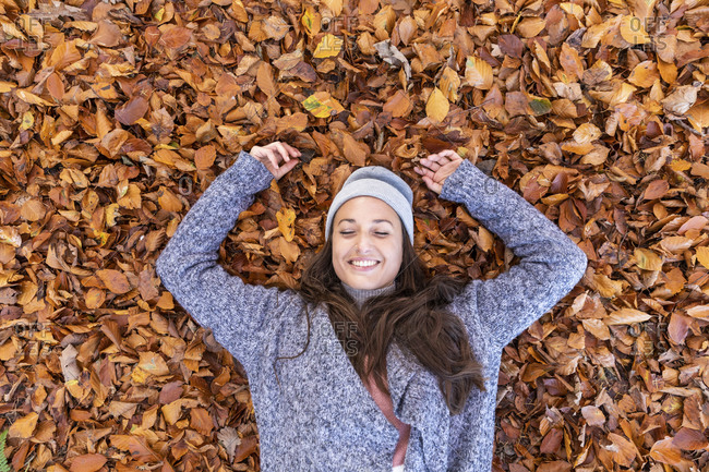 Smiling female hiker lying down on autumn leaves in Cannock Chase woodland
