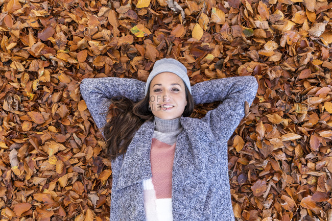 Smiling female hiker with hands behind head lying down on autumn leaves in Cannock Chase woodland