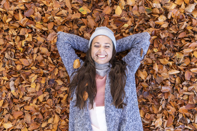 Happy female hiker with hands behind head lying down on autumn leaves in Cannock Chase forest