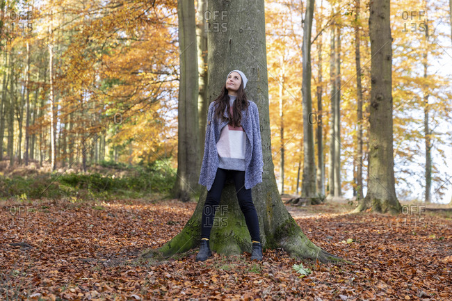 Female explorer standing against tree trunk in Cannock Chase forest