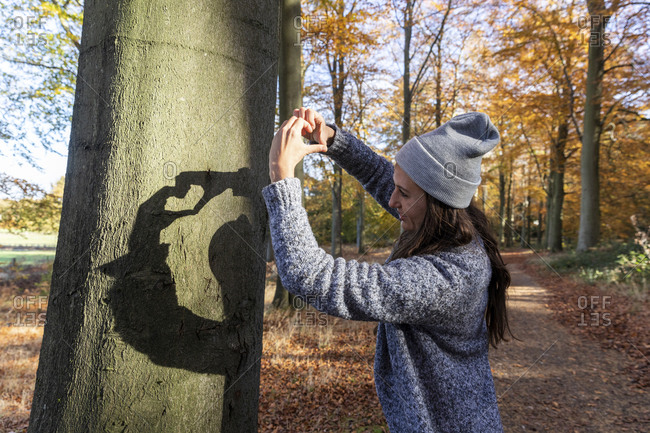 Female hiker making heart shape while standing in Cannock Chase woodland during autumn