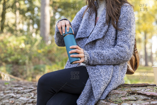 Female hiker holding insulated drink container while sitting in Cannock Chase woodland