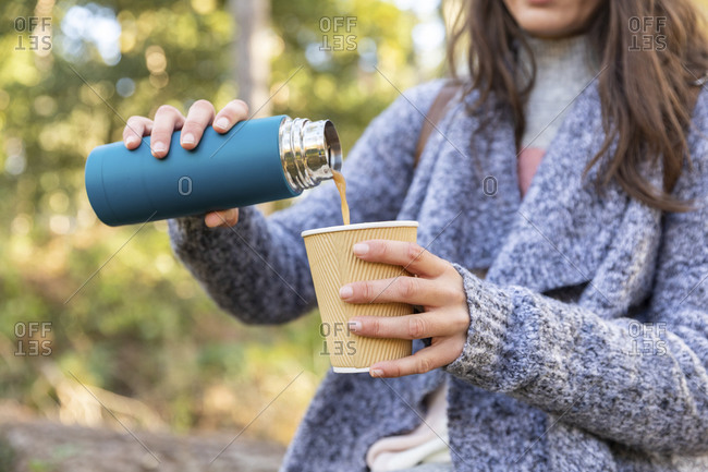 Woman pouring tea from insulated drink container into disposable cup in Cannock Chase forest