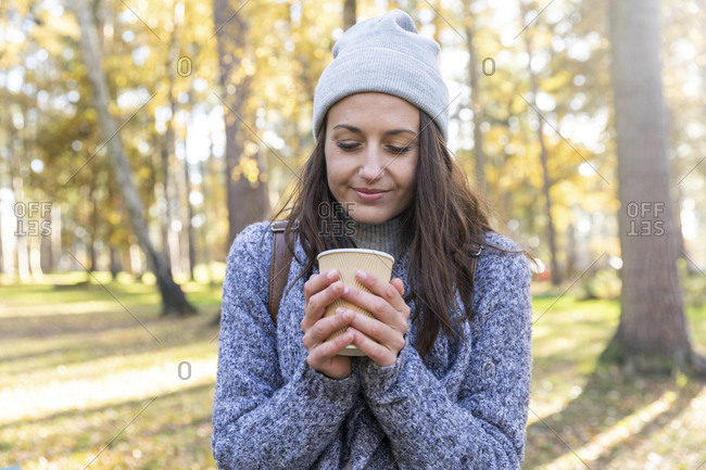 Female hiker holding tea cup in Cannock Chase woodland during winter